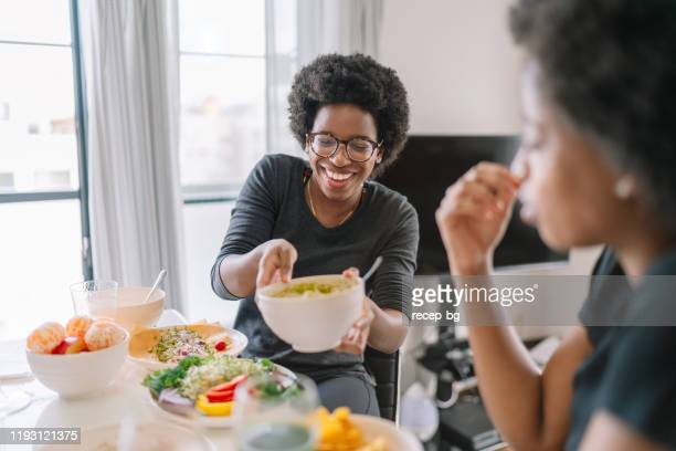 two black women eating vegan food at home - vegetarian food stock pictures, royalty-free photos & images