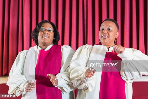 Two black women singing in church choir