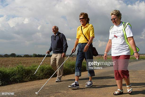 Two blind people walk in the Kent countryside guided by a sighted volunteer from the Kent Association for the Blind The charity organises weekly...
