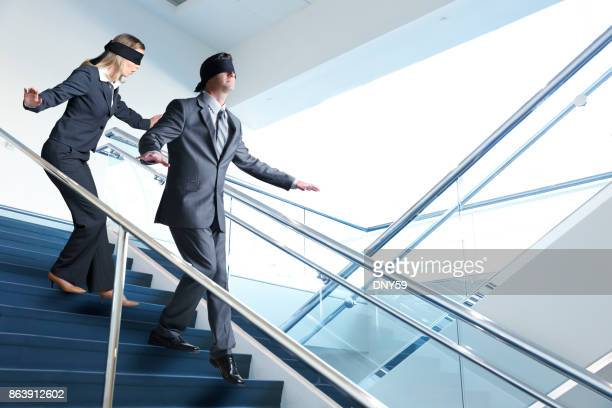 two blindfolded business people navigate staircase - blindfolded stock photos and pictures