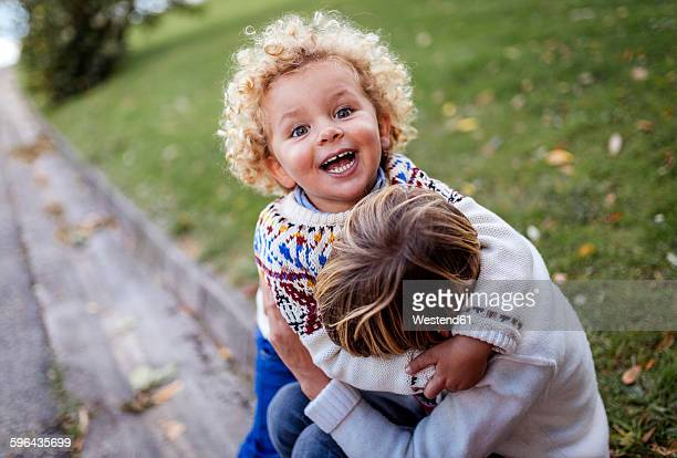 Two blond brother playing together in autumn
