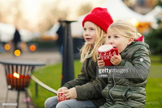 two blonde child sisters drinking hot chocolate at winter european christmas market - traditional festival stock pictures, royalty-free photos & images