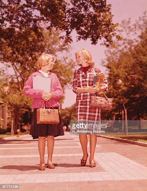 Two blonde female students walking on campus, carrying straw purses and books. (Photo by H. Armstrong Roberts/Retrofile/Getty Images)