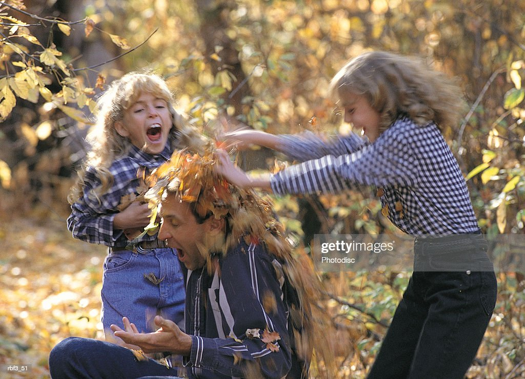 two blonde girls throw leaves on a man sitting on the ground amongst autumn trees loosing leaves : Stockfoto