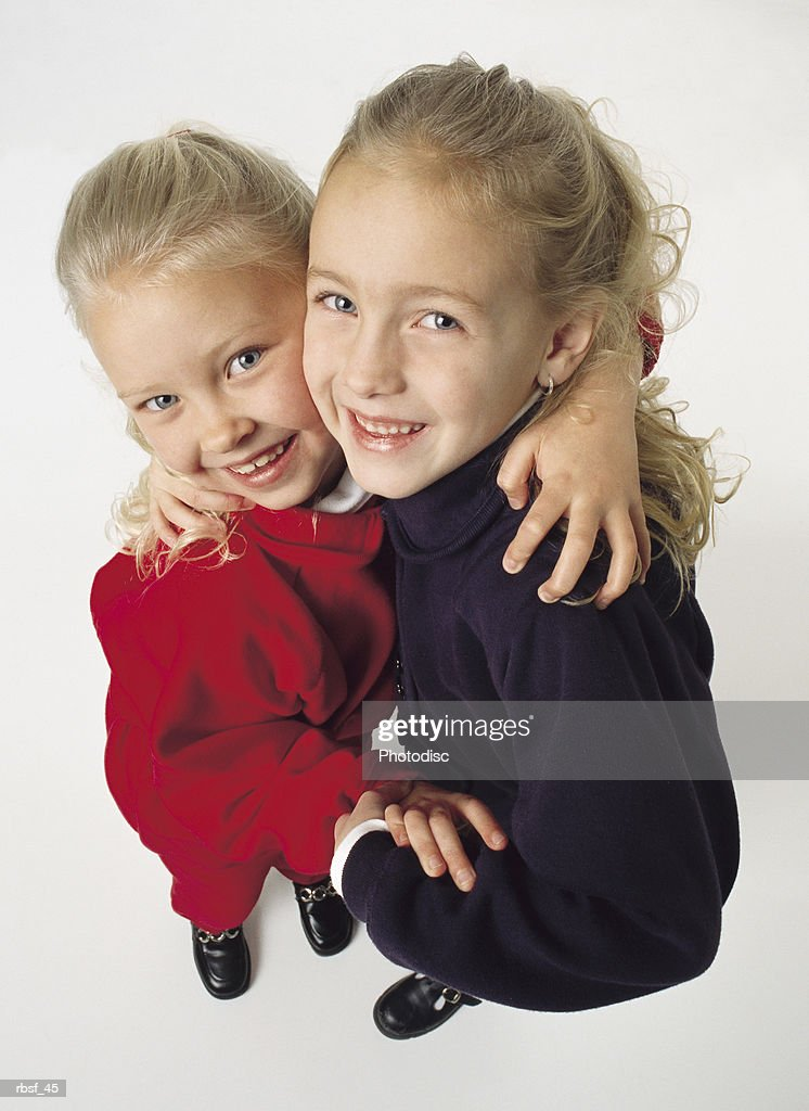 two blonde sisters hold each other and giggle : Foto de stock