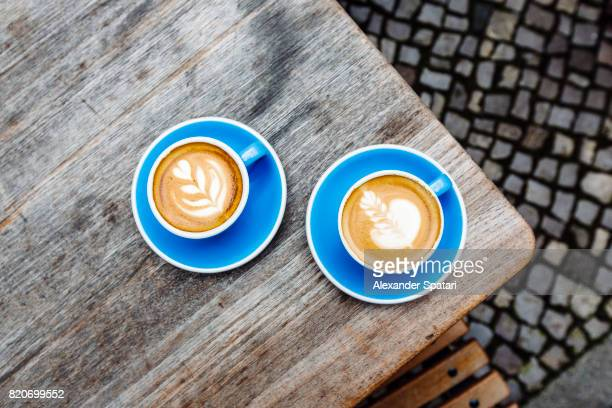 Two blue cups of coffee on the table, high angle view