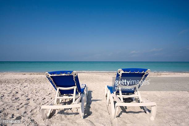 two blue empty beach chairs on white sand facing the ocean - sarasota stock photos and pictures