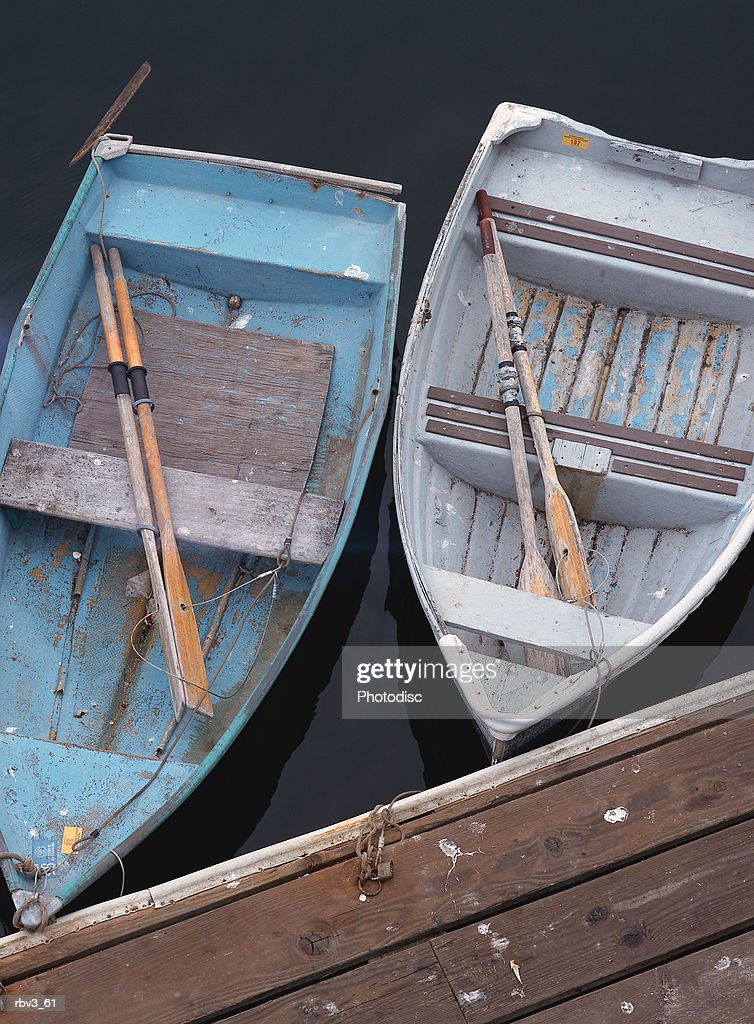 two blue fishing boats with oars float next to each other at the side of a wooden dock : Foto de stock