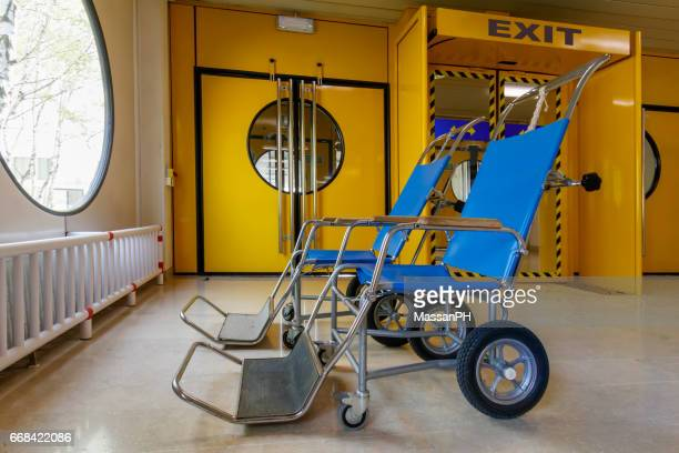 Two blue wheelchairs near the yellow doors of an hospital corridor