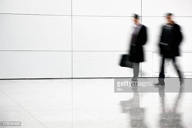 Two blurred businessmen walking in corridor