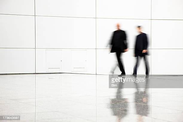 Two blurred businessmen walking in hallway