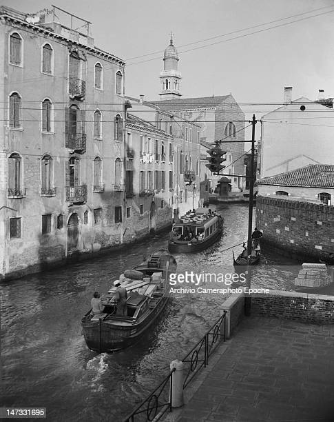 Two boats and a gondola crossing the canal and passing below the traffic light Venice 1951