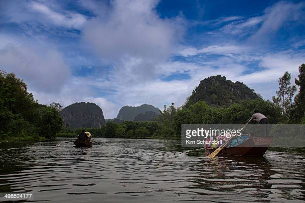 Two boats full of people being rowed down a river in Vietnam with Mountains in the background.