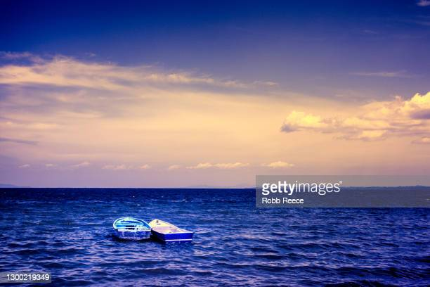 two boats in the ocean with dramatic sky in costa rica - robb reece stock-fotos und bilder