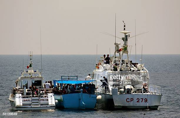 Two boats of Italian Coast Guard take on board illegal immigrants on June 21 2005 in Lampedusa Italy Tens of thousands of immigrants land on the...