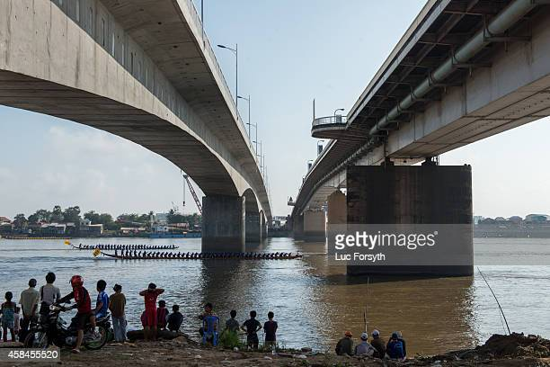 Two boats pass under the Japanese bridge in Phnom Penh during a race during the Water Festival on November 5 2014 in Phnom Penh Cambodia Two million...