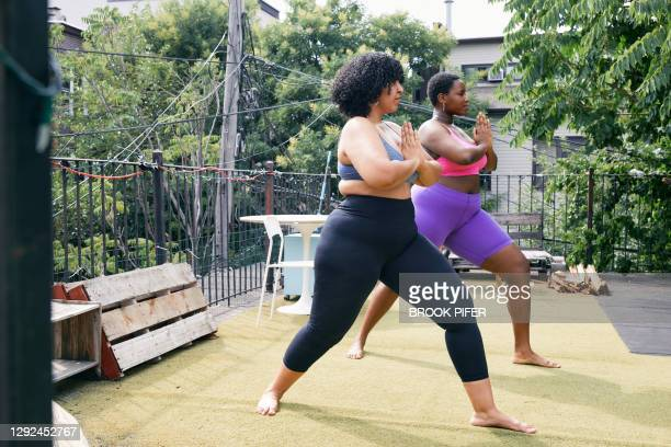 two body positive women practicing yoga together - showus stock pictures, royalty-free photos & images
