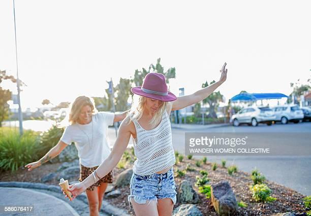 Two Bohemian hipster girls balancing on footpath