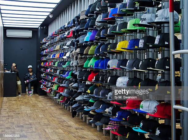 Two bored lads at work in the evening in an urban hat shop located in the recently opened Boxpark in Shoreditch, East London. London, England,...