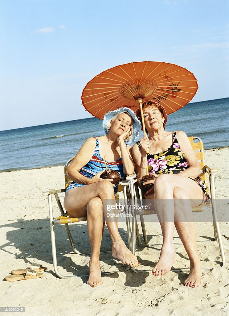 Two Bored Looking Women Sitting on Chairs Under a Parasol : Stock Photo