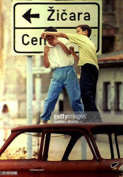 Two Bosnian boys box as they play on the roof of a wrecked car 29 August 1993 The Moslemled Bosnian presidency met early 29 August 1993 to review...