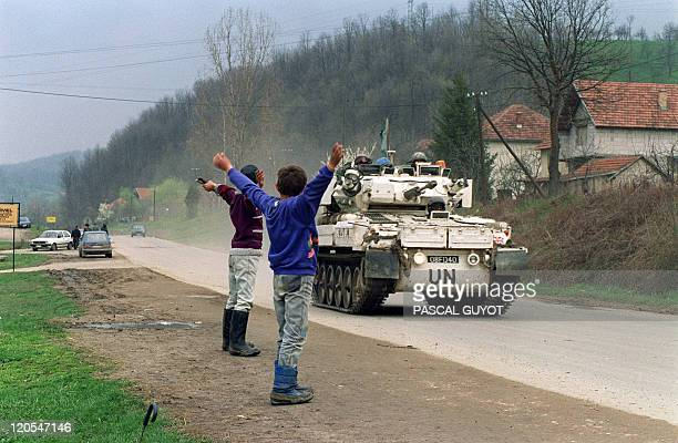 Two Bosnian boys salute a Canadian blue helmets convoy 17 April 1993 near Tuzla departing for the Moslem enclave of Srebrenica where some 30000...