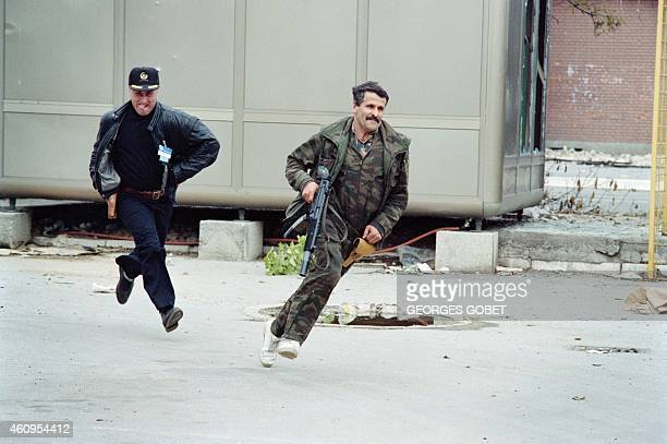 Two Bosnian fighters run for cover to escape shots during fighting in a Sarajevo suburb on June 02 1992