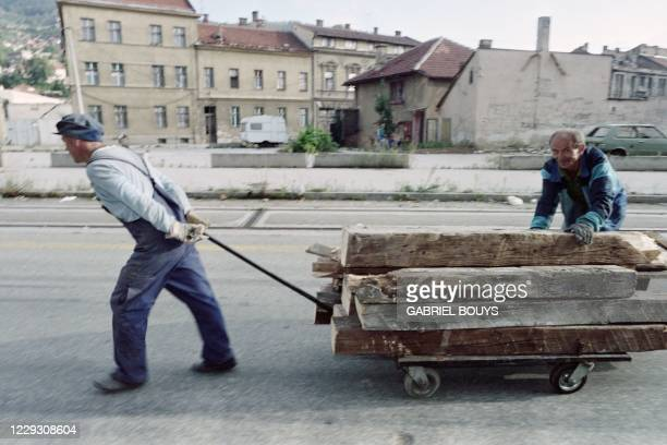 Two Bosnian men push a cart loaded with wood in a dangerous part of Sniper Alley near the Skenderija quarter, wich is close to the Serb positions on...