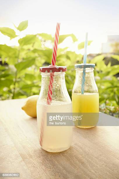 Two bottles lemonade with drinking straws on table