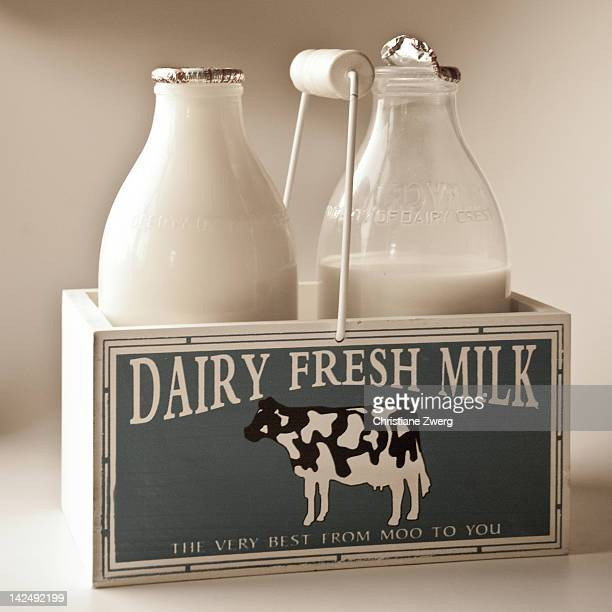 Two bottles of fresh milk in a nostalgic wooden crate.