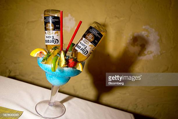 Two bottles of Grupo Modelo SAB Corona Extra beers sit upside down in a blue frozen drink with fresh lemon lime pineapples and a strawberry at a...
