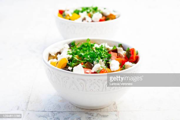 two bowl of grilled eggplant and bell peppers with goat cheese and parsley - larissa veronesi stock-fotos und bilder