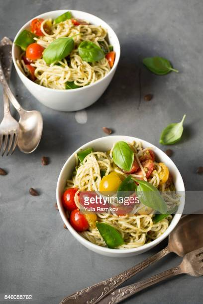 Two bowles of spaghetti with vegetables