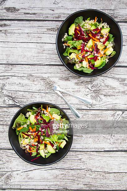 Two bowls of autumnal salad with lettuce, carrots, avocado, beetroot, seeds, pomegranate and quinoa