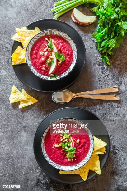 two bowls of beetroot soup garnished with apple slices, peanuts and flat leaf parsley served with tortilla chips - flat leaf parsley stock pictures, royalty-free photos & images