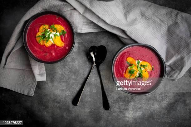 two bowls of beetroot soup - larissa veronesi stock-fotos und bilder