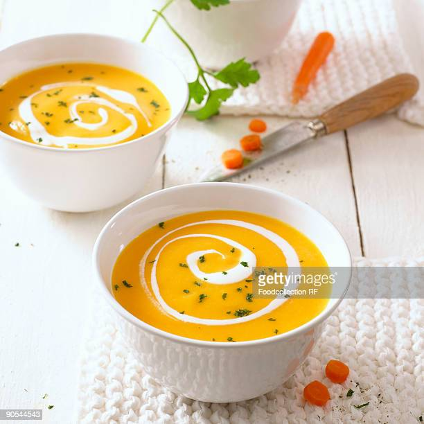 Two bowls of carrot soup with swirls of cream, close up