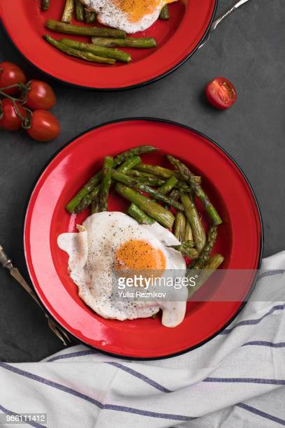 Two bowls of green grilled asparagus with tomato and eggs