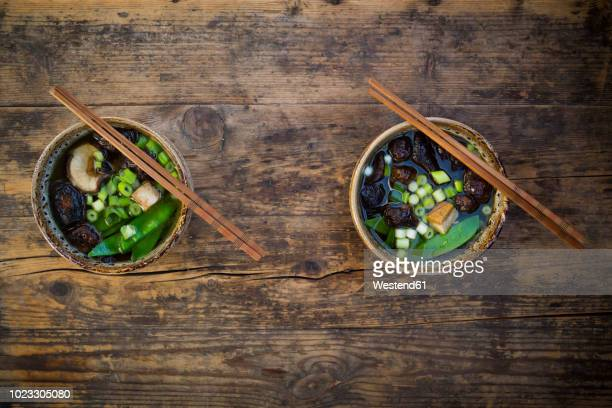 two bowls of japanese miso soup with sugar peas, shitake mushrooms, tofu and mung sprouts - japanese food stock pictures, royalty-free photos & images
