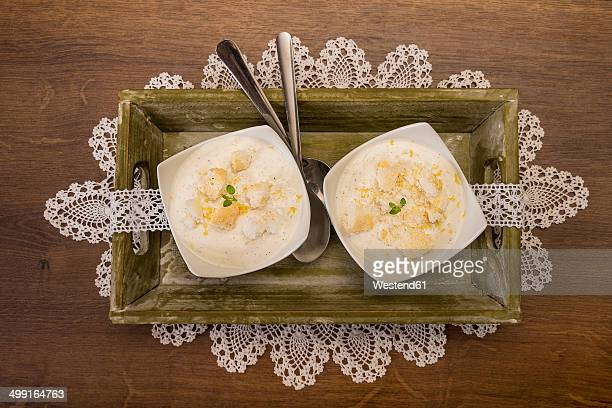 Two bowls of lemon curd creme with crumbled meringues on tablet and wooden table, elevated view