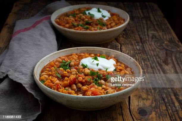 two bowls of red lentil soup with chickpeas - larissa veronesi stock-fotos und bilder