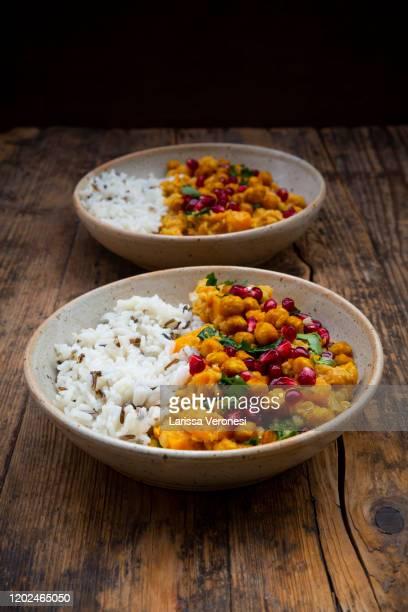two bowls of sweet potato lentil curry with basmati rice - larissa veronesi stock-fotos und bilder