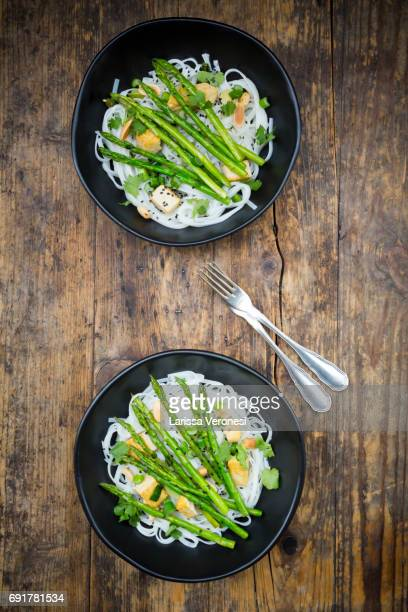 Two bowls of vegan Pad thai with mini green asparagus and tofu