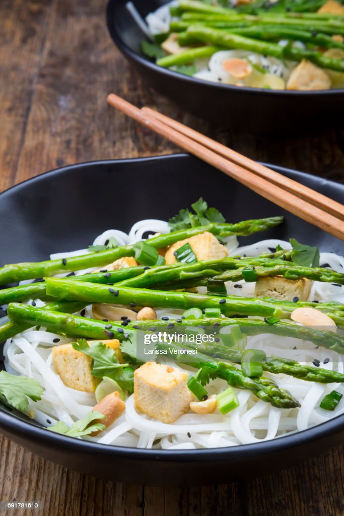 Two bowls of vegan Pad thai with mini green asparagus and tofu : Stock-Foto