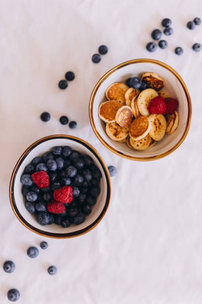 Two bowls seen from directly above filled with berries and healthy snacks
