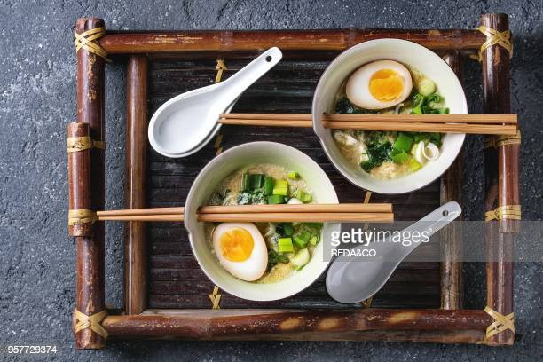 Two bowls with asian style soup with scrambled eggs half of marinated egg spring onion spinach served with wood chopsticks and spoons on bamboo tray...