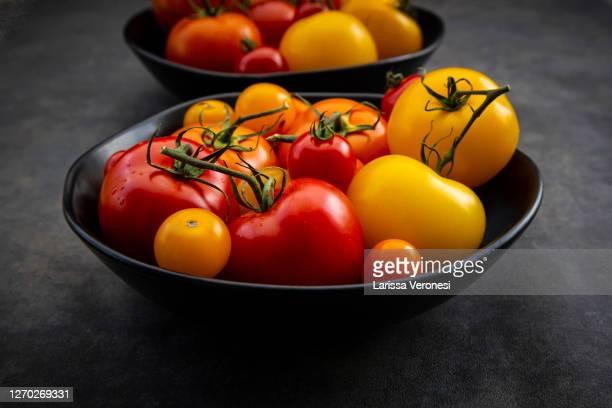 two bowls with tomatoes - larissa veronesi stock-fotos und bilder