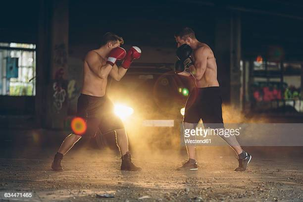 Two boxers fighting in an abandoned factory