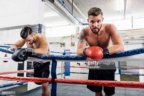 Two boxers resting in boxing ring