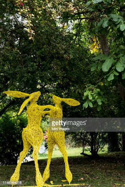 Two boxing hares on hind legs, a tall garden sculpture painted in yellow.